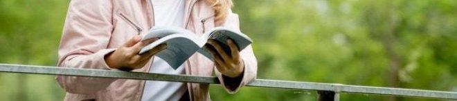 Lektorin mit aufgeklapptem Buch an einer Brücke